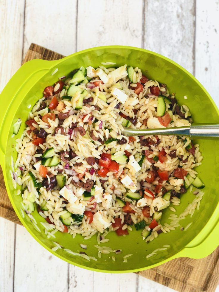 homemade greek orzo pasta salad in a large Joesph Joseph green bowl