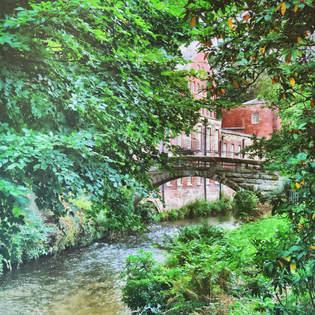 self care ideas - going for a walk - image of the bridge over the River Bollin at Quarry Bank Mill in Cheshire