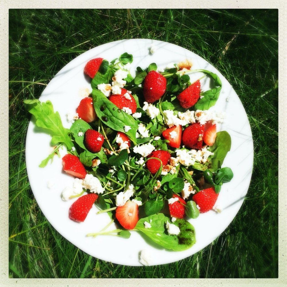platter of strawberry and feta salad tossed with spinach, rocket and herbs and dressed in simple balsamic salad dressing.