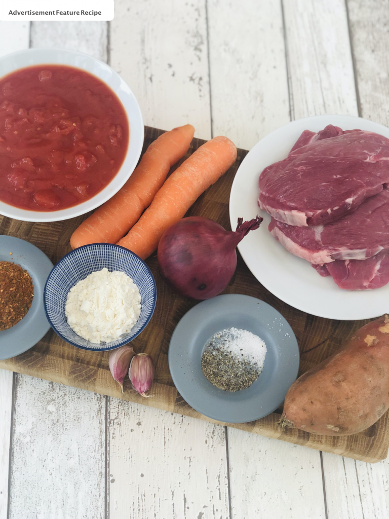 ingredients for moroccan lamb stew -lamb, red onion, carrots, tinned tomatoes, moroccan seasoning, flour, salt and pepper and garlic on a wooden chopping board