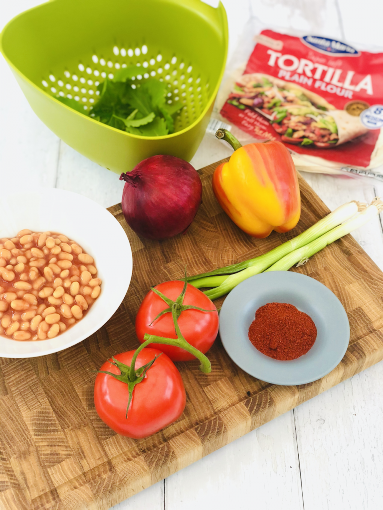 ingredients for baked beans fajitas - baked beans, vine tomatoes, spring onions, pepper, red onion, smoked paprika, salad leaves and a pack of tortilla wraps