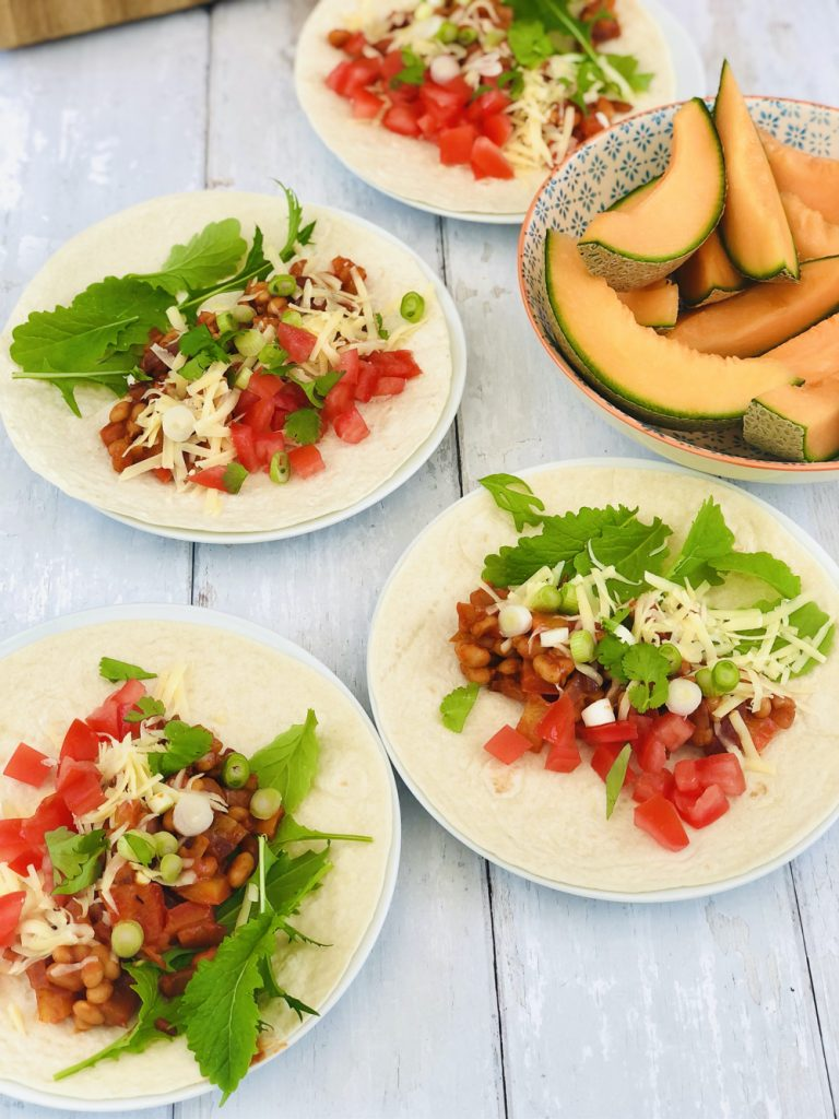 baked bean fajitas served with salad, chopped tomatoes and grated cheese, bowl of melon slices alongside