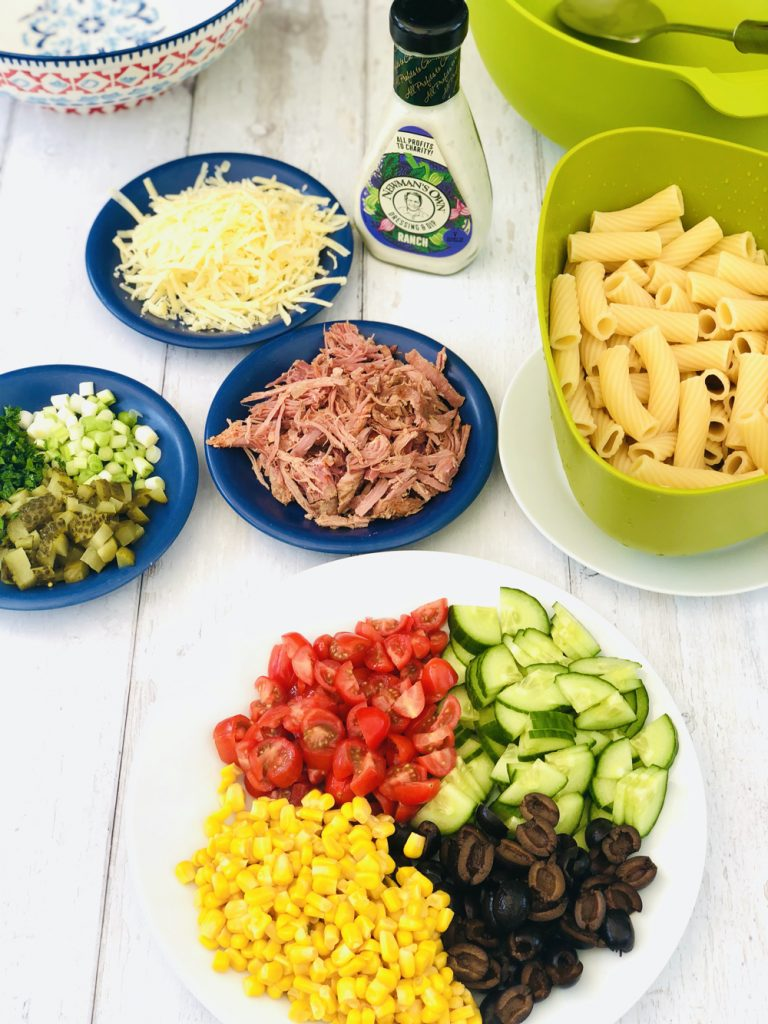 ingredients for ranch pasta salad - pasta, shredded ham, grated cheese, tomatoes, cucumber, sweetcorn, olives, spring onions, jalapeño and chopped parsley along with a bottle of ranch dressing