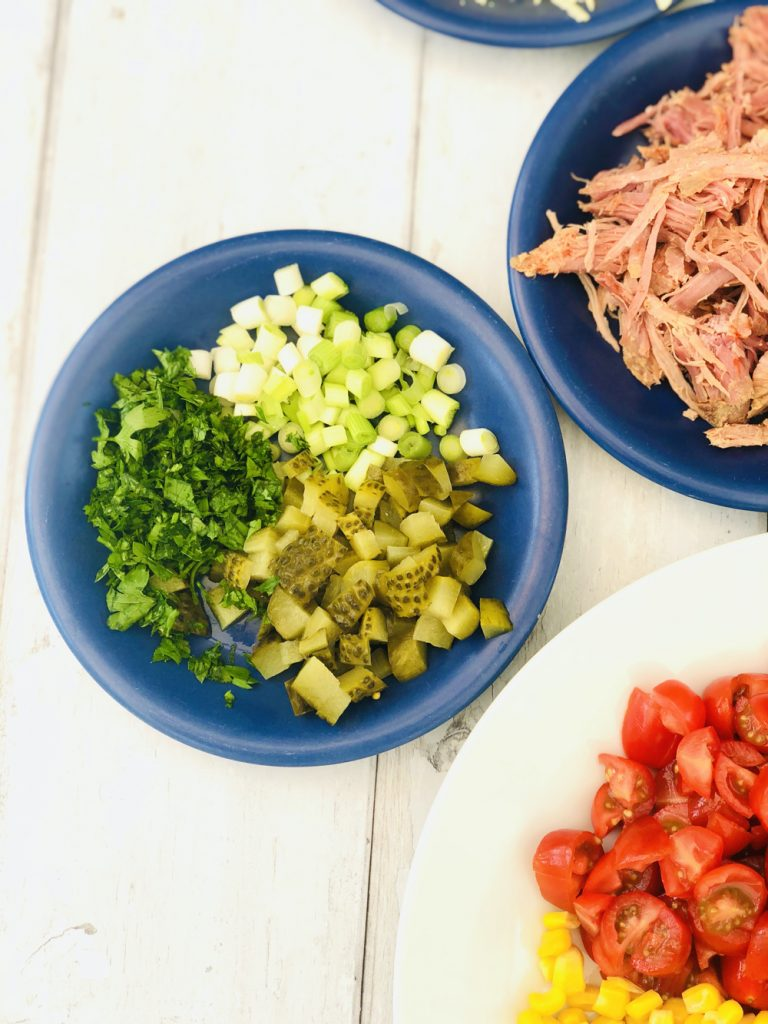 salad chopped spring onions, chopped dill pickle and chopped flat leaf parsley, plate of shredded ham in the background