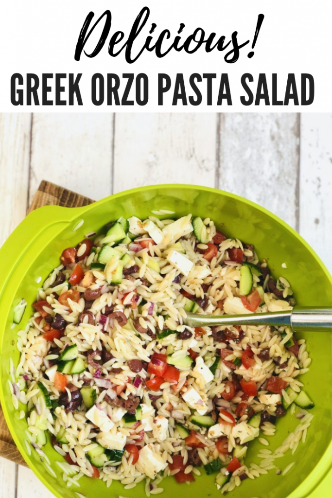 """greek orzo pasta salad in a large green bowl. Text overlay reads """"delicious greek orzo pasta salad"""""""