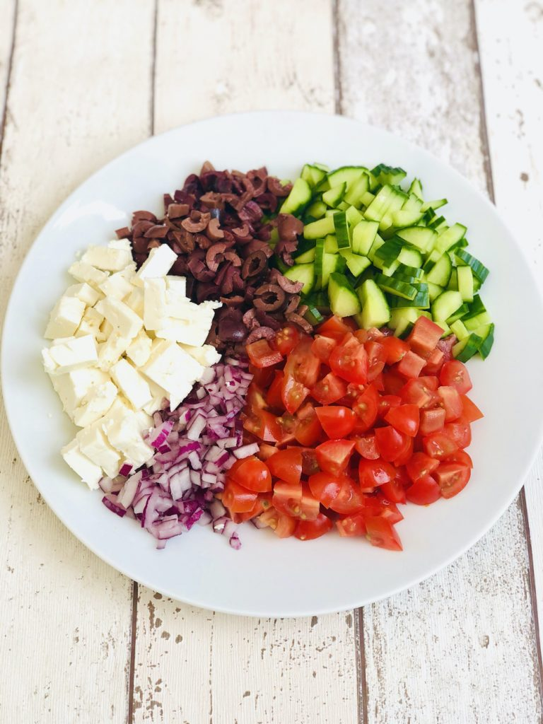 large white plate filled with Greek salad ingredients - chopped tomatoes, diced red onions, chopped feta cheese, black olives and diced cucumber