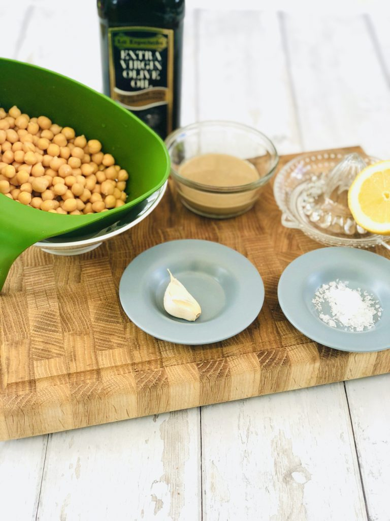 ingredient for easy homemade hummus - tin of drained chickpeas, tbs of tahini, bottle of olive oil, garlic clove, sea salt and half a lemon all together on a wooden chopping board