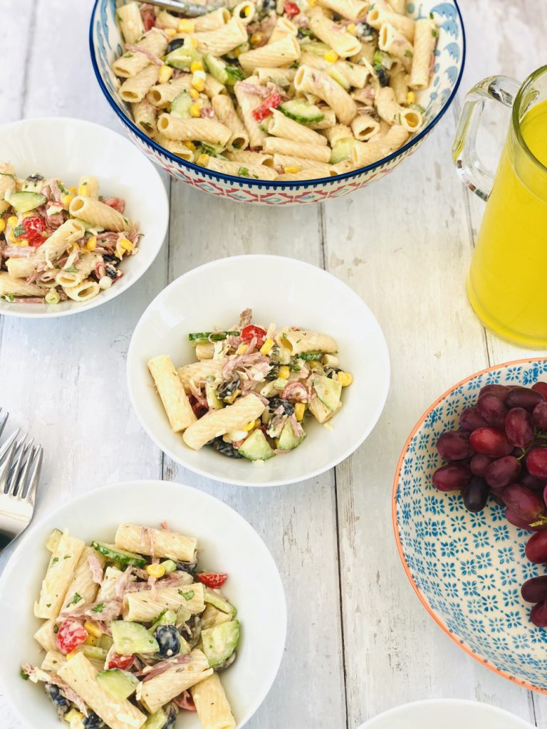 ranch pasta salad in white bowls - jug of orange cordial and bowl of grapes are on the table by the pasta