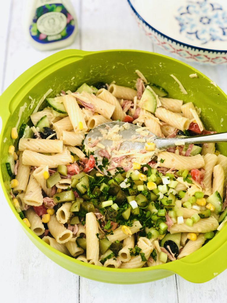 chopped parsley, dill pickles and spring onions being added to ranch pasta salad in a green bowl