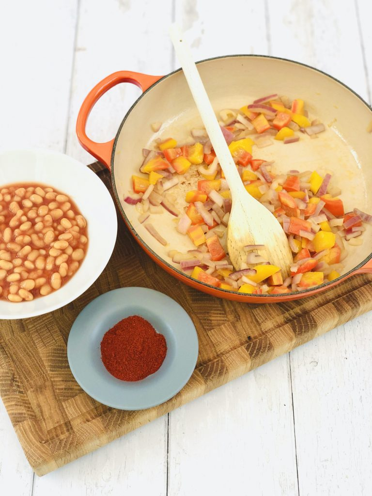 cooked red onion and peppers in a skillet pan next to a bowl of baked beans and saucer with smoked paprika on