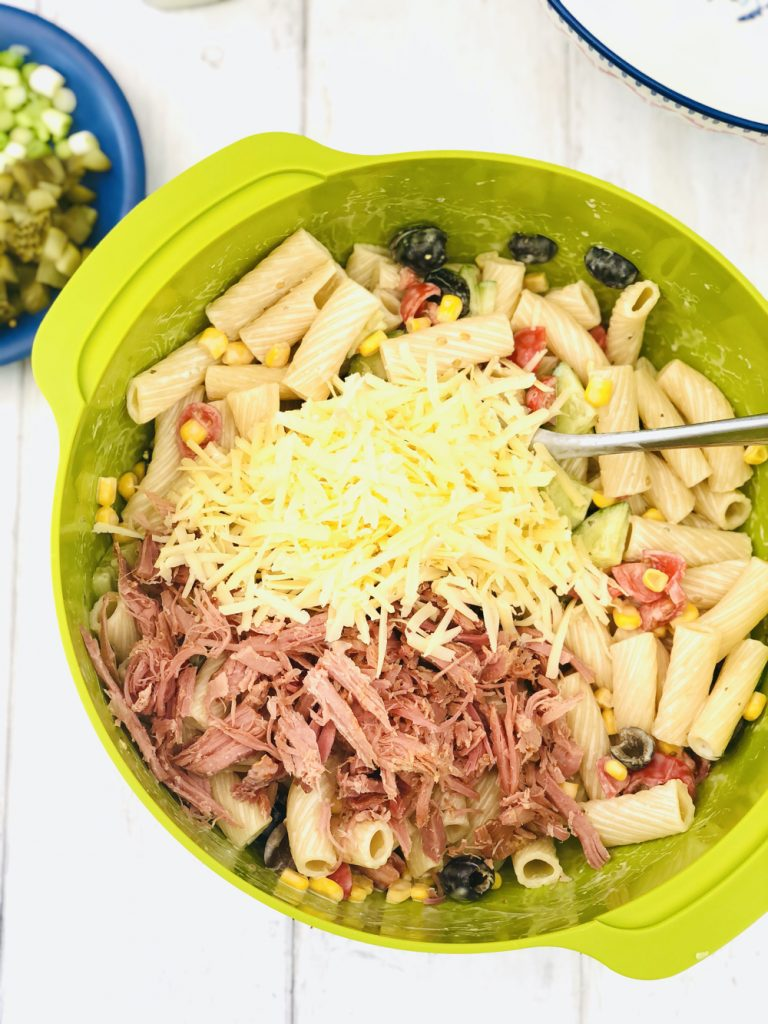 shredded ham and cheese being added to ranch pasta salad in a green mixing bowl