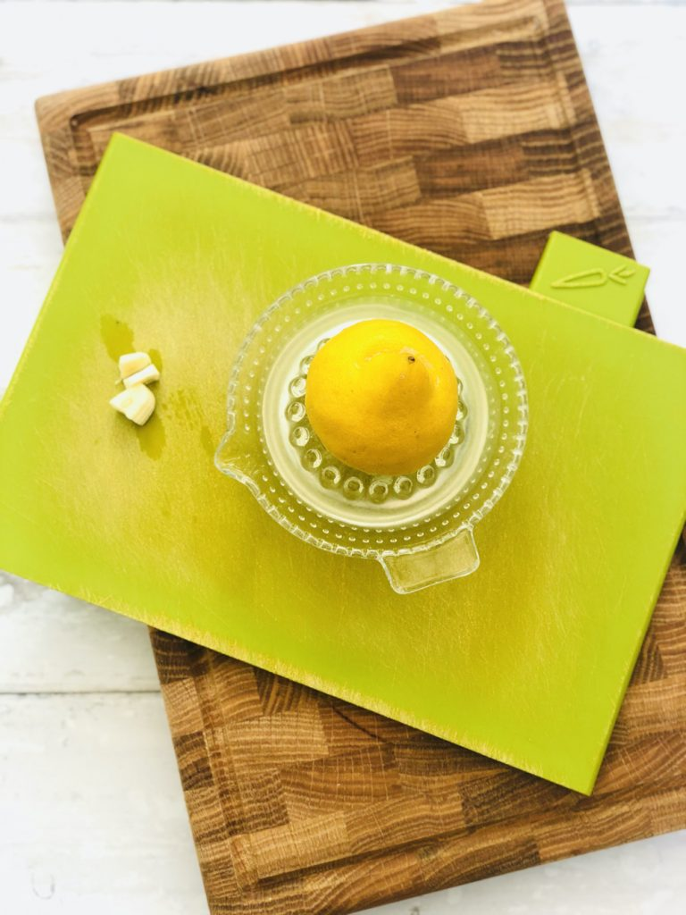 half a lemon being juiced on a glass juicer on a bright green jospeh joseph chopping board
