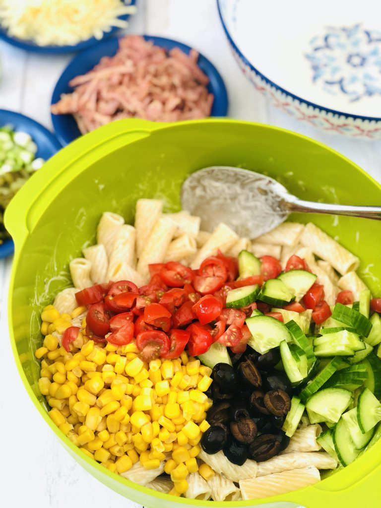 chopped baby plum tomatoes, sweetcorn, chopped black olives and diced cucumber being added to ranch coated rigantoni pasta in a green mixing bowl