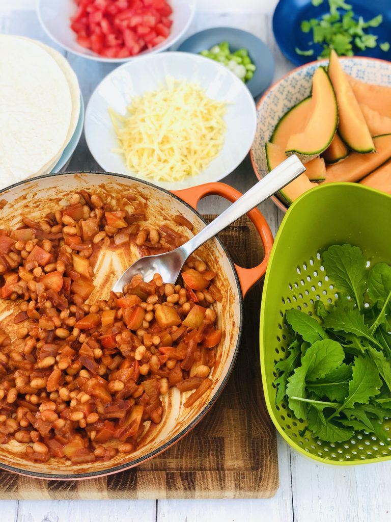 baked bean fajita filling in a skillet pan with small bowls of fajita toppings surrounding it - salad leaves, grated cheese and chopped tomatoes