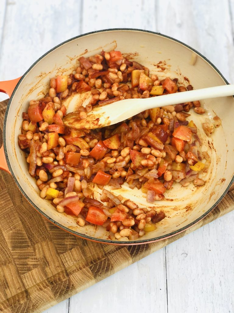 baked beans, red pepper and onions with smoked paprika all mixed together in a skillet pan