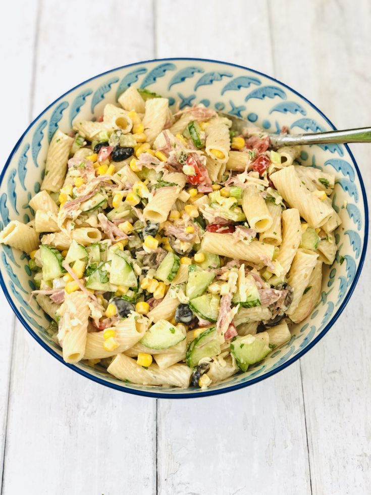easy ranch pasta salad in a blue and white serving bowl on a white table