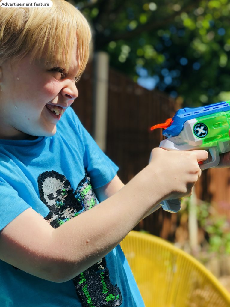 boy playing with a zuru x-shot micro fast fill water blaster in the garden