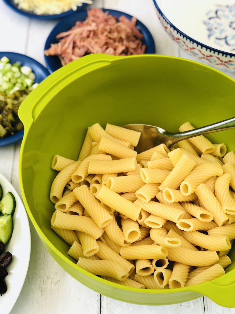 rigatoni pasta being drained in a bright green joseph jospeh colander
