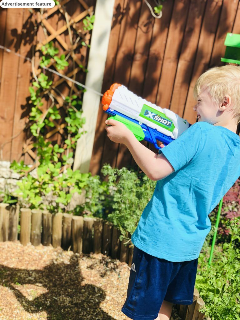 boy playing with a Zuru X-Shot fast fill water blaster in the garden