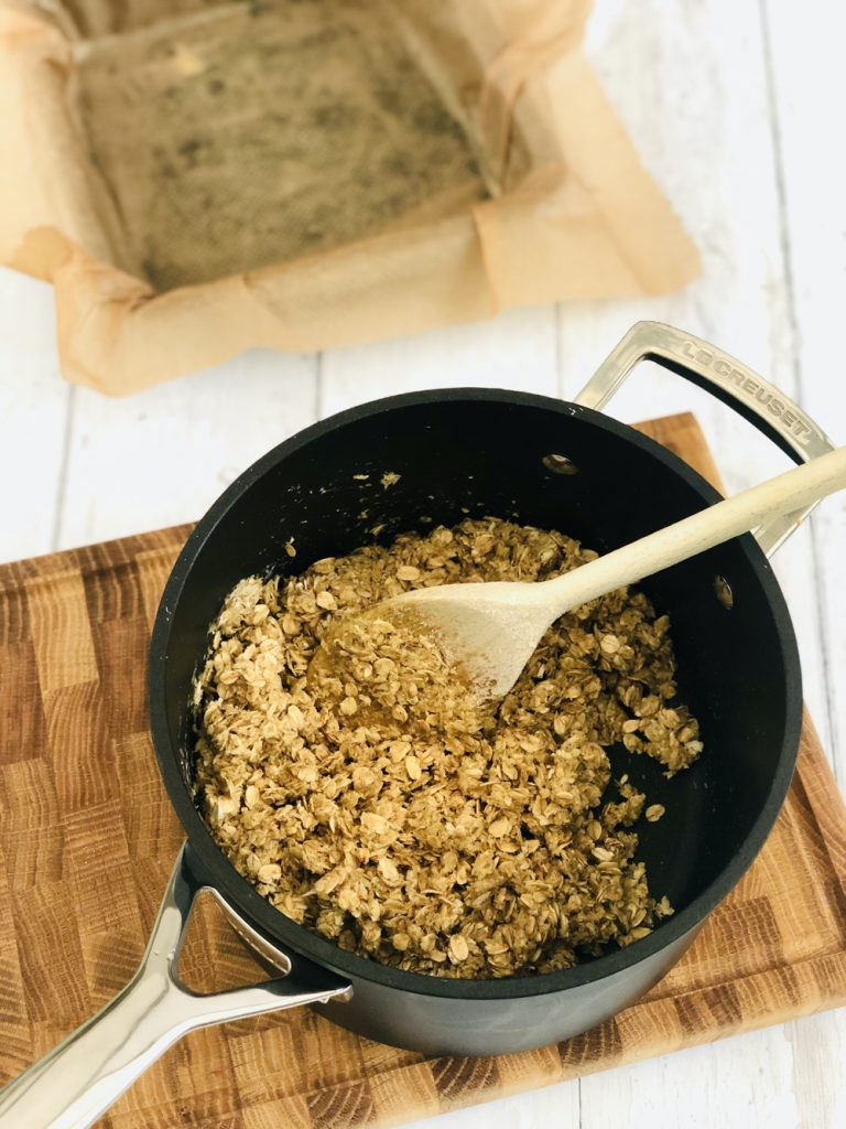 Le Creuset saucepan with oats stirred into melted butter, brown sugar and golden syrup