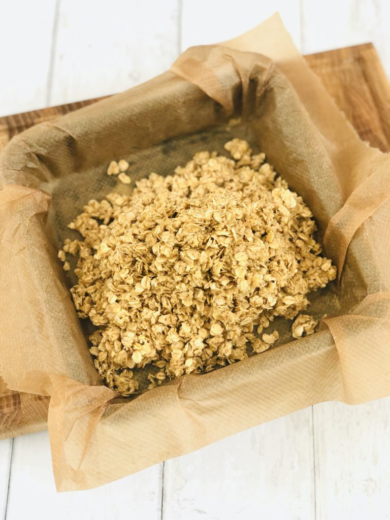 flapjack mixture tipped into square baking tin