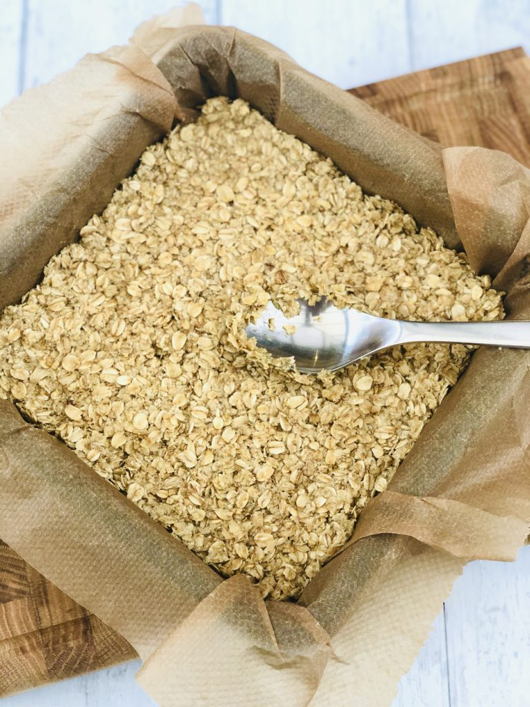 buttery oats all pressed down in square baking tin