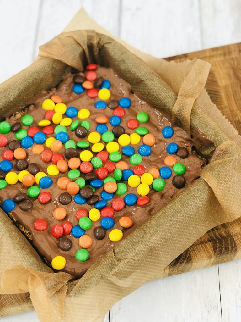 coloured M&M's sprinkled over the top of chocolate coated flapjacks