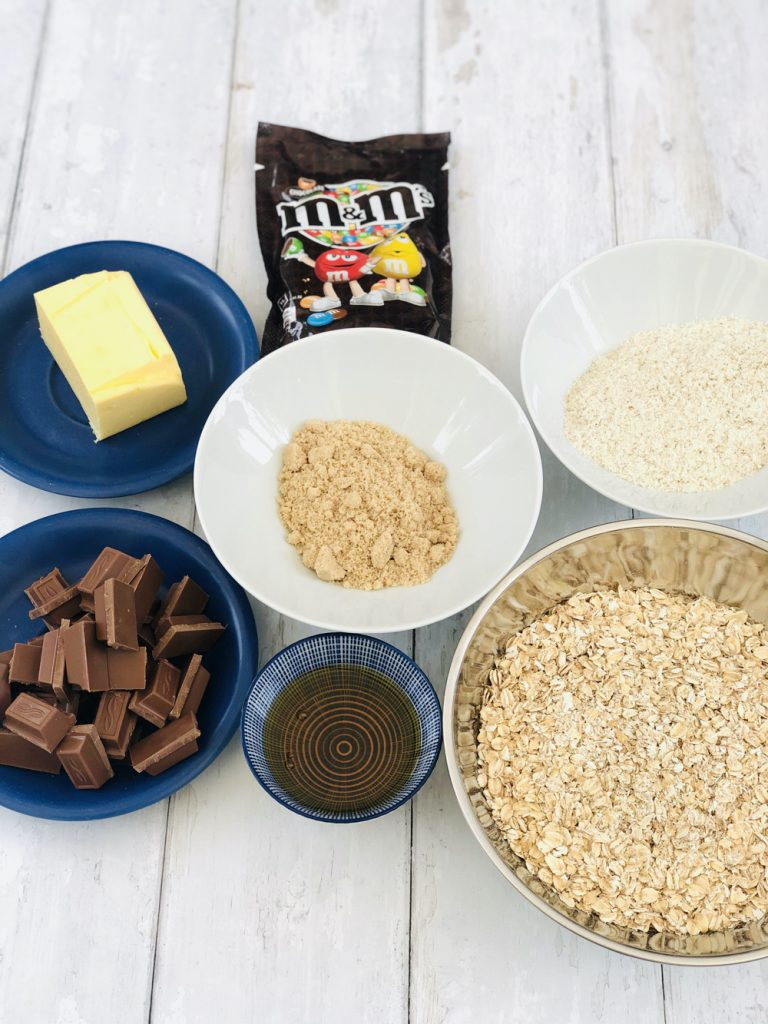 ingredients for M&Ms Chocolate flapjacks, oats, ready brek, chocolate, butter, syrup and brown sugar along with pack of M&M's