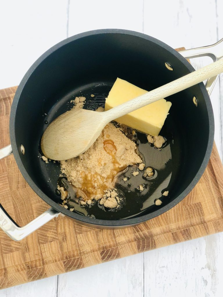 Le creuset black saucepan with brown sugar, syrup and butter in the bottom being stirred with a wooden spoon