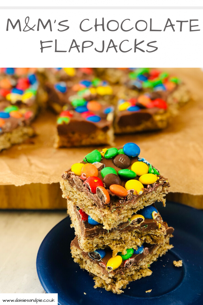 "stack of M&M's chocolate flapjacks on a blue plate. Text ""M&M's chocolate flapjacks"""