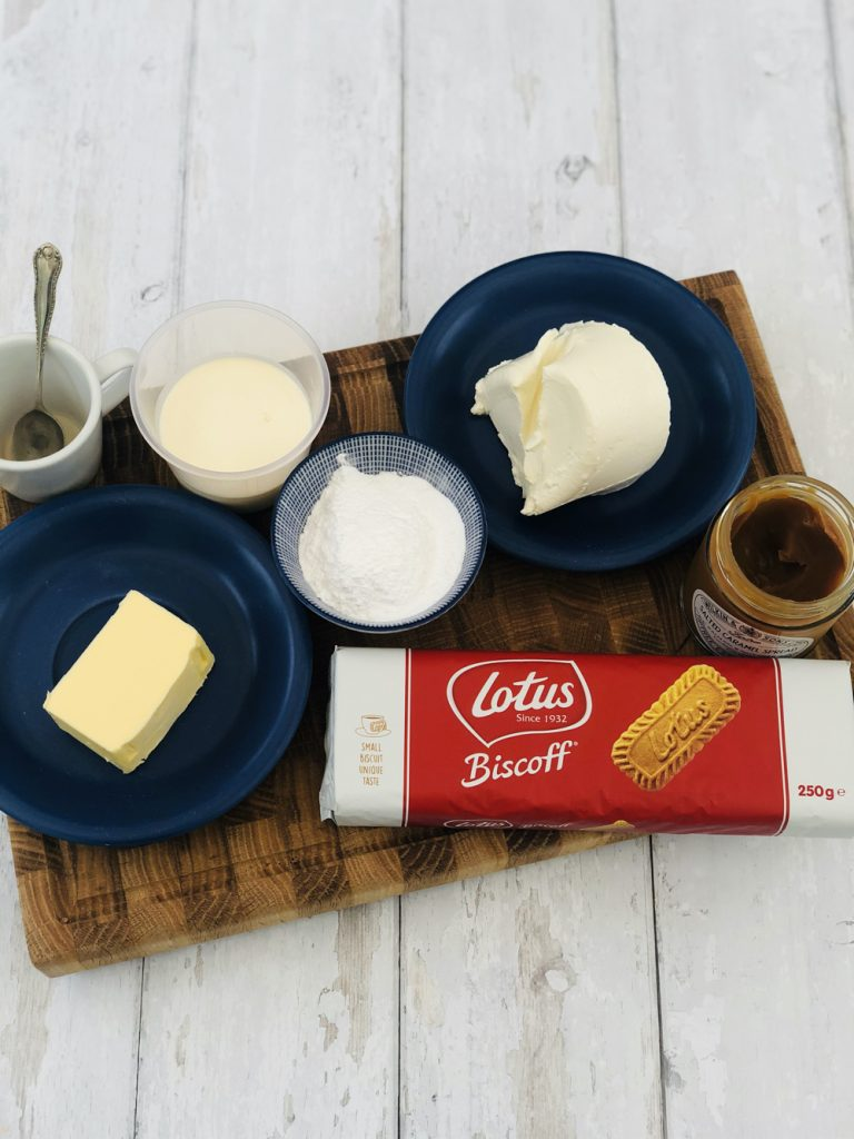 ingredients for mini biscoff cheesecakes - lotus biscuits, butter, cream cheese, icing sugar, vanilla extract, salted caramel sauce and double cream on a wooden board on white wooden table.