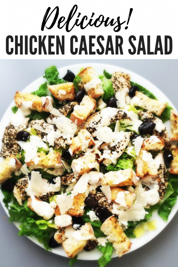 """chicken caesar salad platter topped with crunchy homemade croutons. Text overlay """"delicious chicken caesar salad"""""""