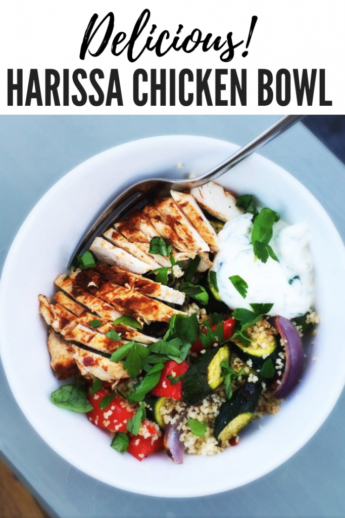 """harissa chicken breast in a bowl with vegetable couscous and herby lemon yogurt. Text overlay reads """"delicious harissa chicken bowl"""""""
