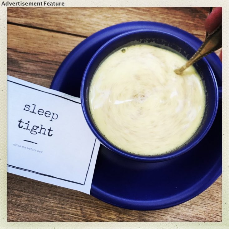 turmeric milk in a dark blue cup with a little note saying sleep tight