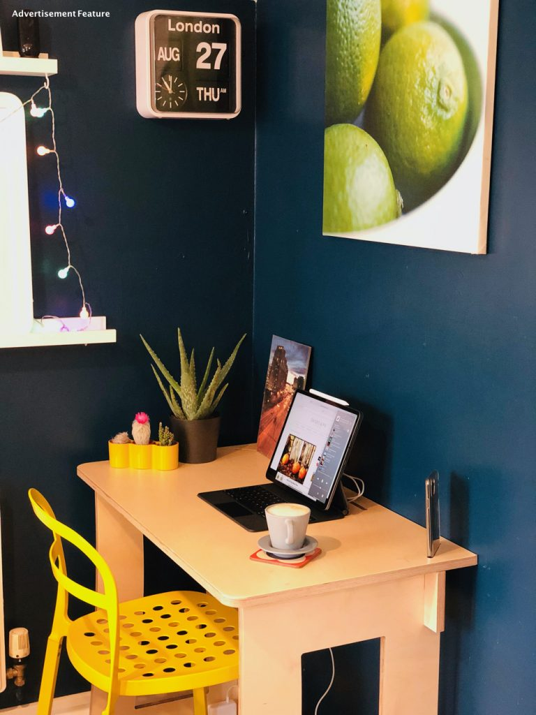 small home office desk - 60 second desk from clever closet in the corner of the kitchen. Desk has a yellow IKEA chair at it. On the desk is a iPad pro with keyboard, and iPhone 11 pro max, along with a pot pant, a set of 3 cactus in a yellow pot. Above the desk is a picture of limes and a clock with the time and date on it.
