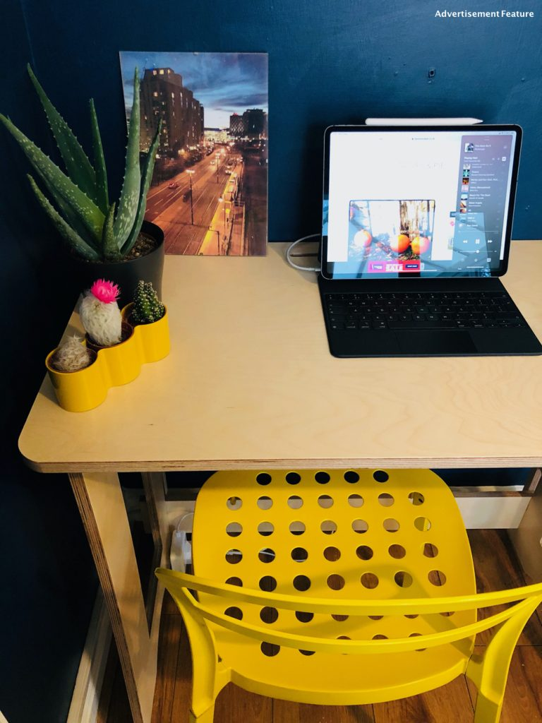 60 second desk from clever closet . With yellow IKEA chair, iPad pro with keyboard, pot plant and set of three cactus in a bright yellow pot. Image of Salford quays taken by Andy Mallins Photos is in the background