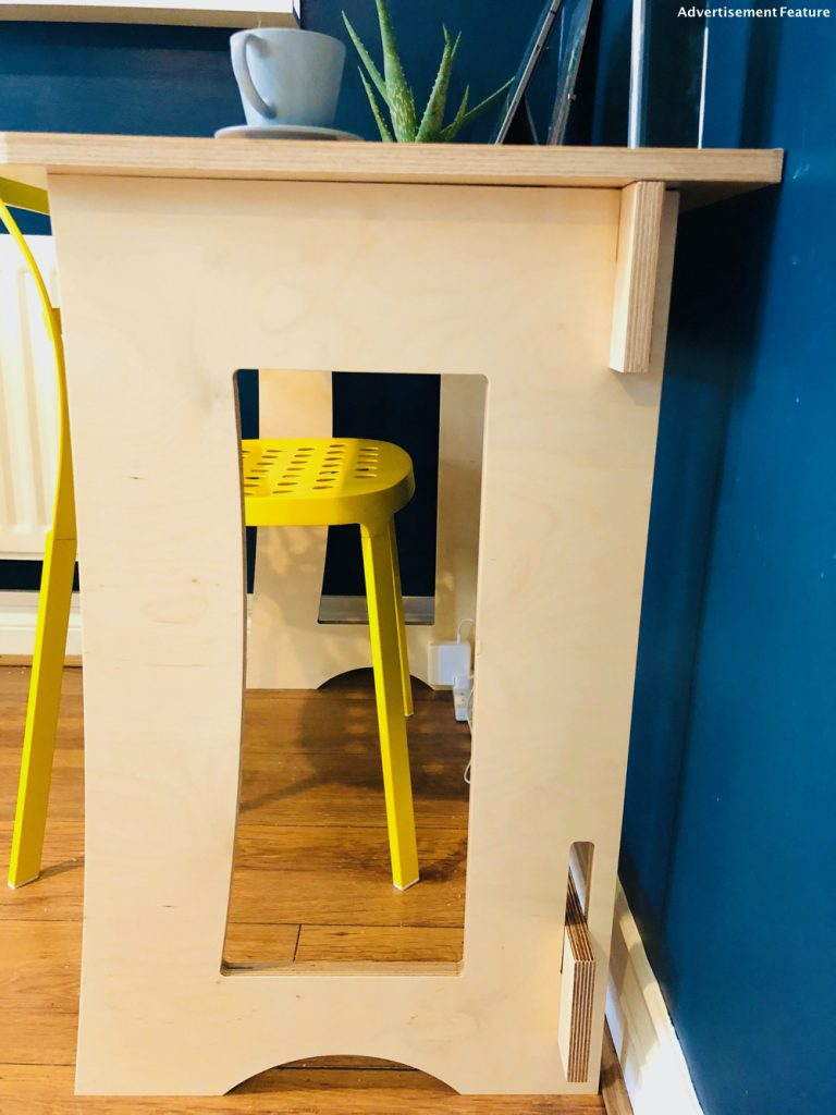 small home office desk - 60 second desk from clever closet in the corner of a kitchen, with a yellow IKEA chair at the desk - cup of coffee and iPhone 11 on top of desk