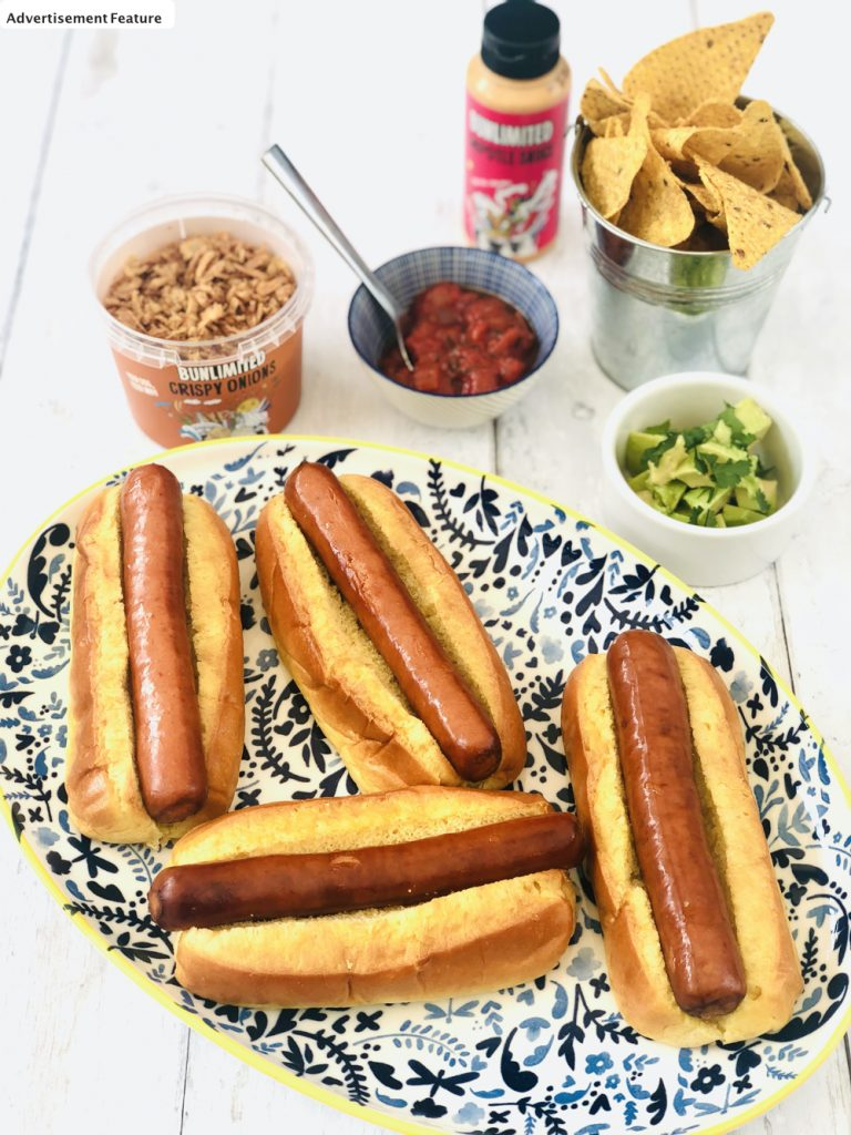 Mexican hotdogs ingredients - brioche rolls, hot and spicy hotdogs, bunlimited crispy onions, tomato salsa, avocado cubes, bucket of nachos and unlimited chipotle sauce