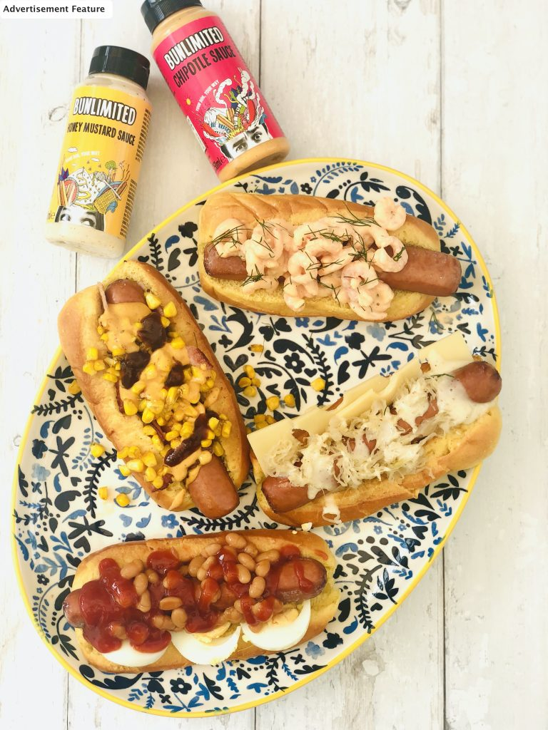 loaded gourmet hotdogs with bunlimited chipotle sauce and bunlimited honey mustard sauce alongside the hotdogs