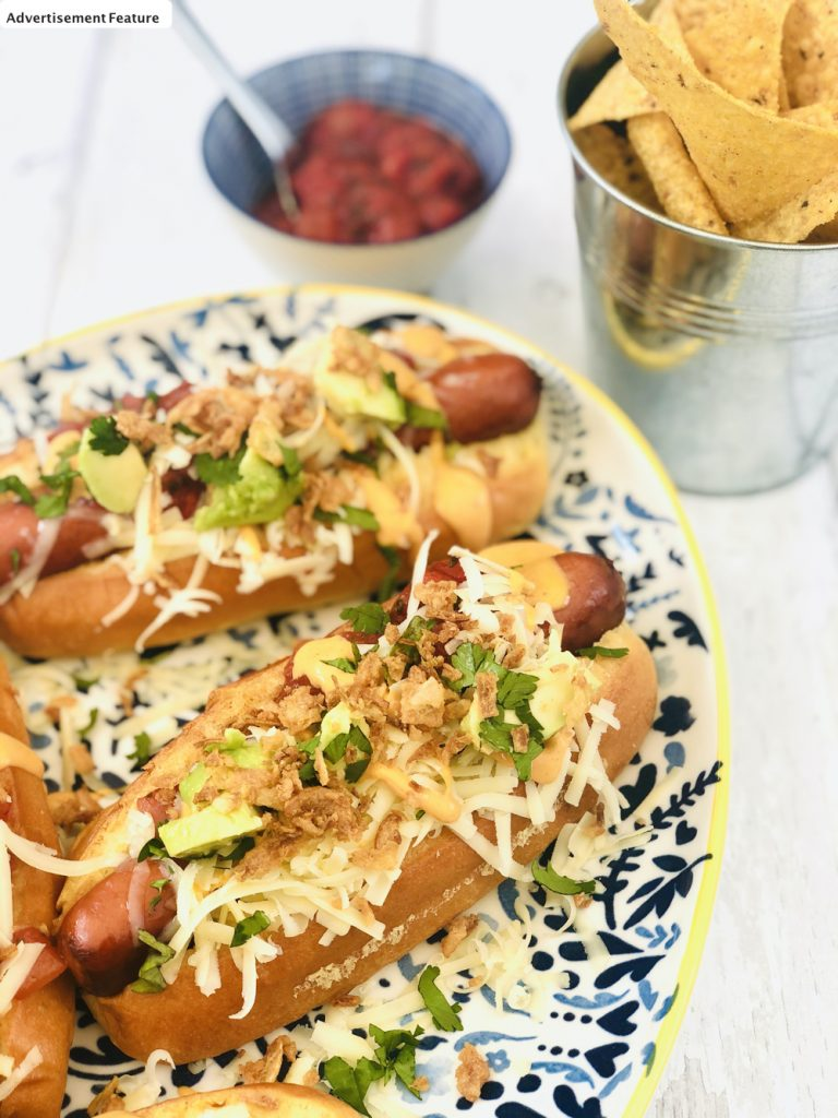 Mexican hotdogs - soft brioche rolls stuffed with hot and spicy hotdog sausages topped with chipotle sauce, cheese, salsa and avocado, served with crispy onions and a side of nachos