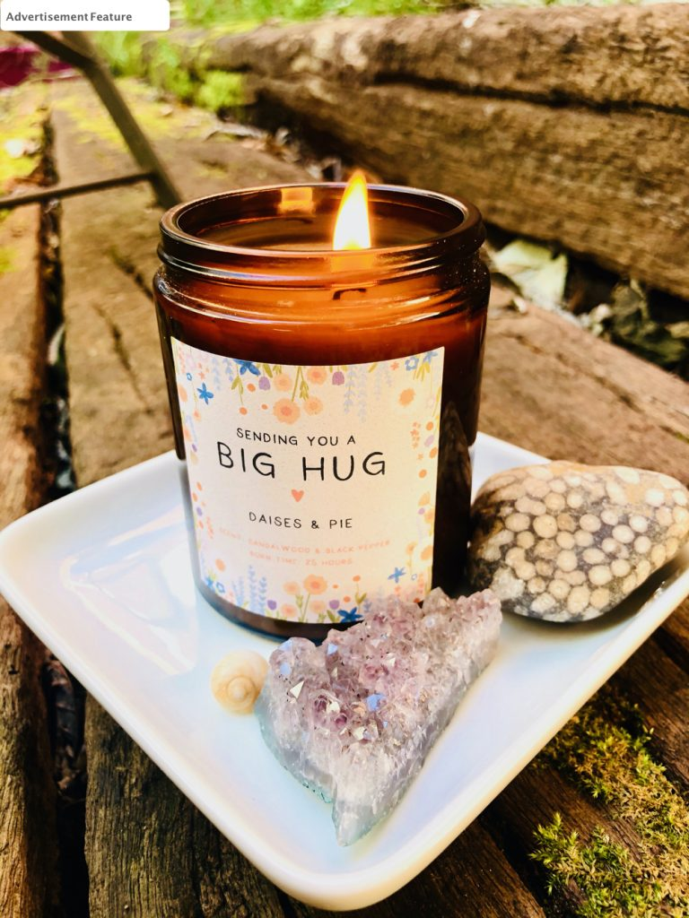 Kindred Fire - Scented Candle in sandalwood and black pepper fragrance. Candle is stood on a white square ceramic plate next to a piece of amethyst and a circle stone.