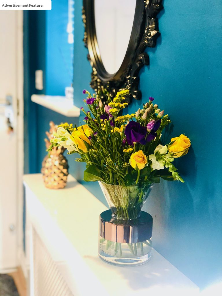 Bloom and Wild letterbox flowers arranged in a glass vase with gold detail. Vase is on a hallway shelf with a golden pineapple and black rimmed ornate mirror against a dark rich blue wall colour