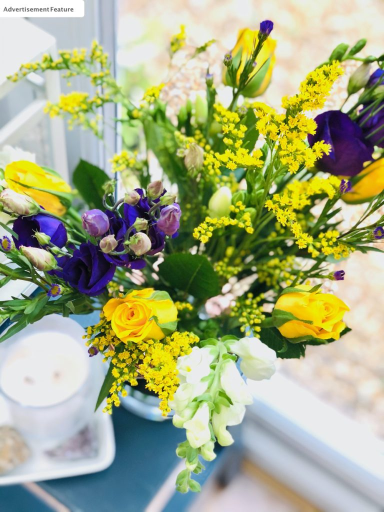 Bloom and Wild letterbox flowers arranged in a glass vase with gold detail. Vase is on a small table in the sunshine next to a white double wick candle