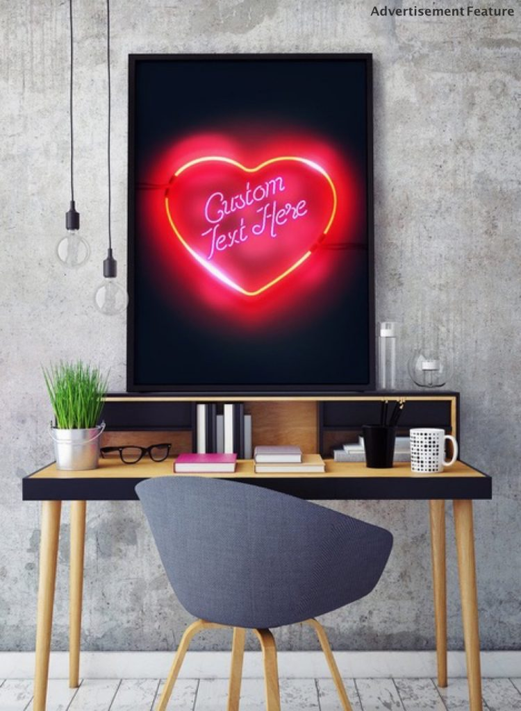 customisable neon word print from Ink and Drop - pink glowing heart on a black background on the wall above a desk with grey chair