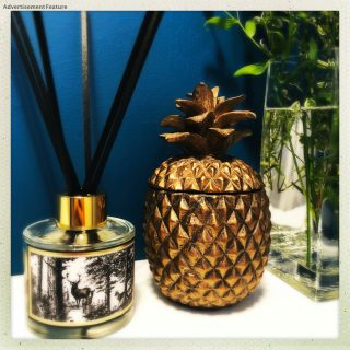 chase and wonder enchanted forest reed diffuser next to a bronze pineapple ornament and vase of flowers