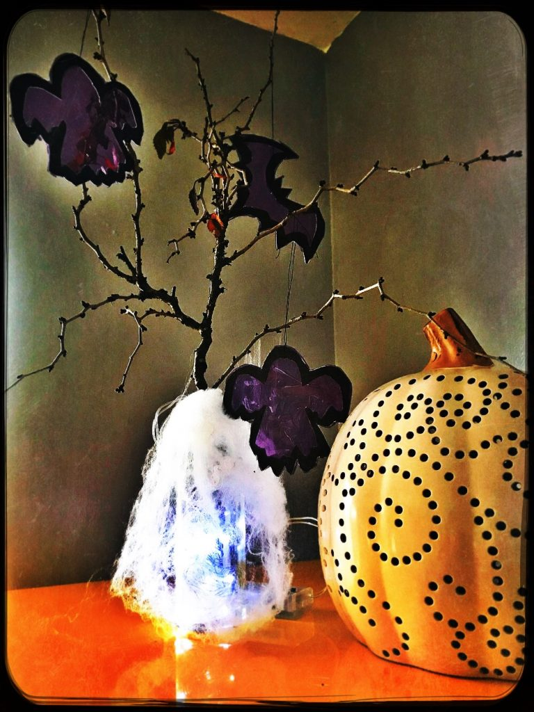 DIY Halloween tree made from painted twigs and decorated in homemade halloween tree decorations in the shape of ghosts made with purple cellophane. halloween tree is by a decorated pumpkin.