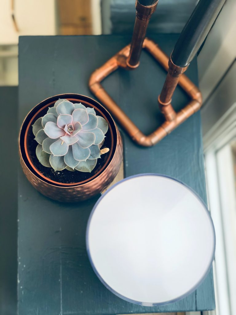 Philips Hue Go Portable Light on a dark blue stool with a succulent plant and copper piping candlesticks