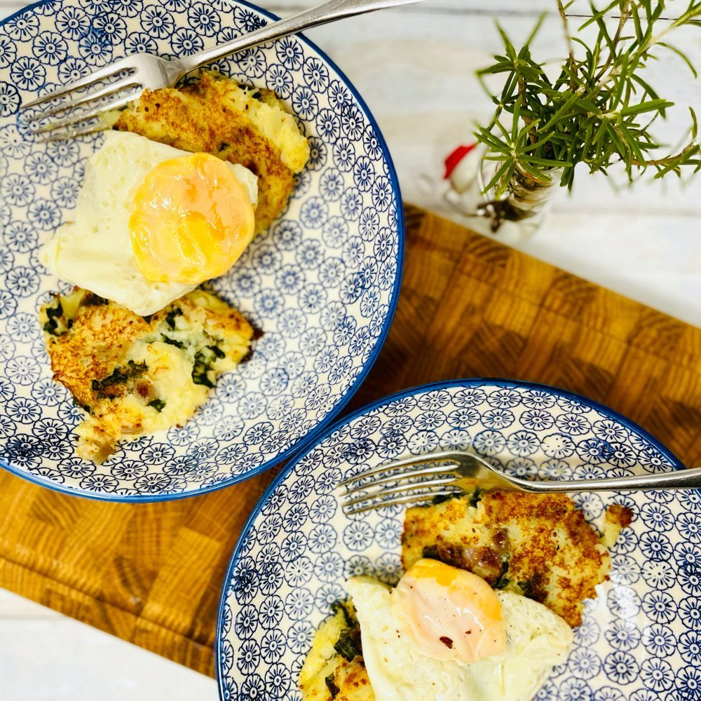bubble and squeak served topped with fried eggs. Two blue and white bowls filled with bubble and squeak with eggs on a wooden board. Small pot of rosemary stood at the side.