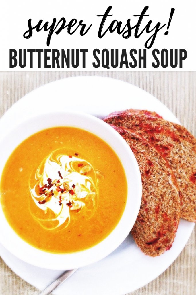 "bowl full of homemade roasted butternut squash soup served with a swirl of creme fraiche and sprinkle of chilli flakes. On the side is some delicious beetroot bread ready for dunking. Text overlay ""super tasty roasted butternut squash soup"""