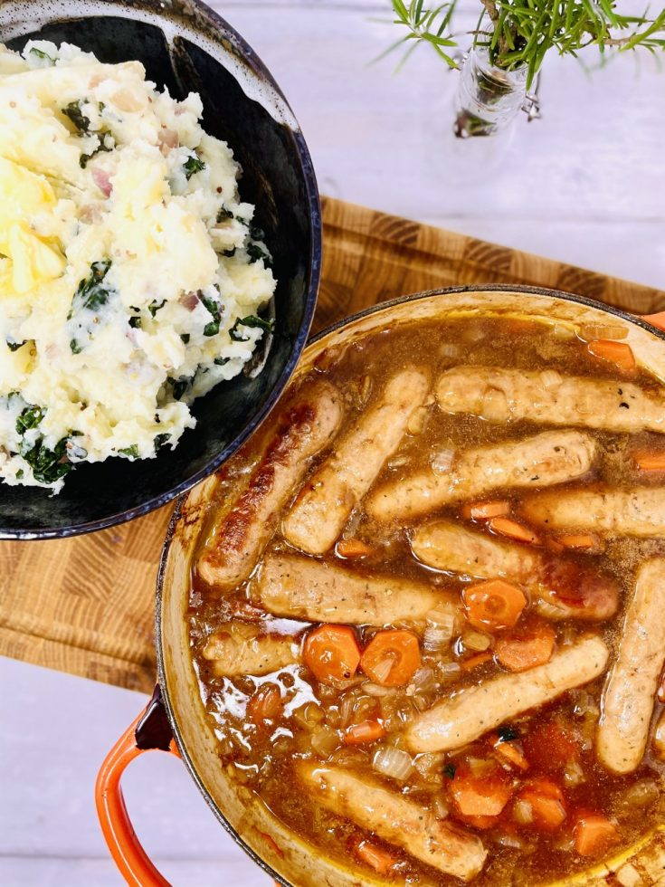 sausage and cider casserole in a big enamel pan with bowl of colcannon potatoes next to it ready to be served